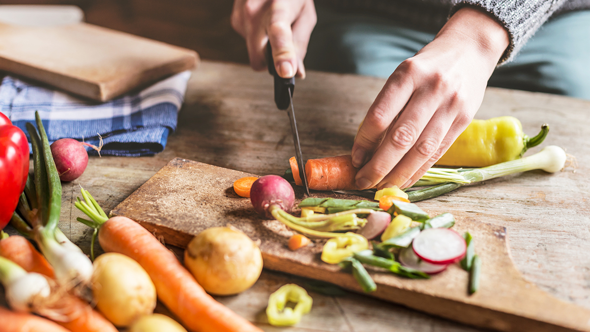Close up of hands cutting vegetables on a cutting board.