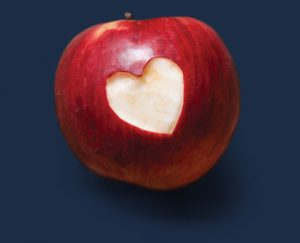 Red apple with a heart shaped hole in the skin.