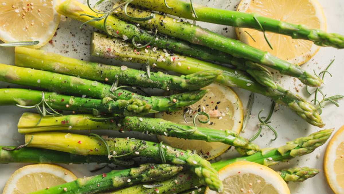 Cooked asparagus with sliced lemon.